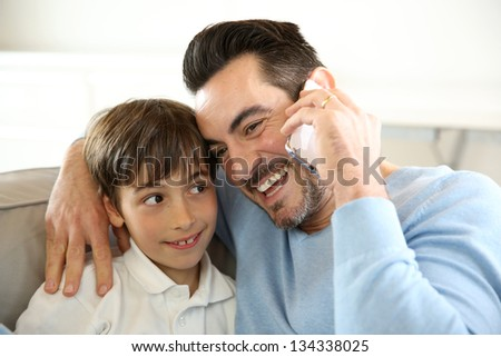Little boy with dad playing with smartphone - stock photo