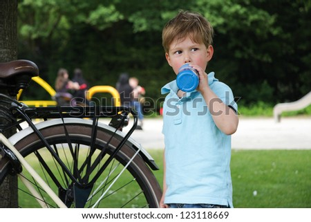 Little boy with drinking bottle getting refreshed on a hot summer day and standing next to a bike in a park - stock photo