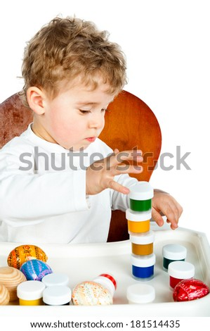 little boy with Easter eggs and paint isolated on white - stock photo