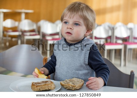 Little boy with eating bread and apple in kindergarten for breakfast