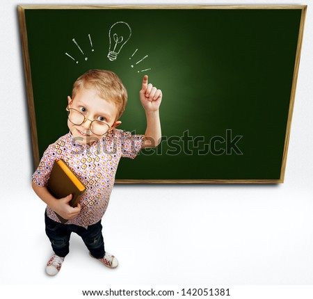 Little boy with eurica gesture standing near green schoolboard - stock photo