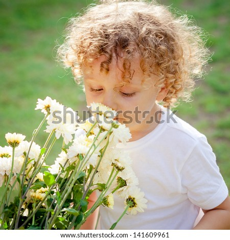 little boy with flowers in hand - stock photo