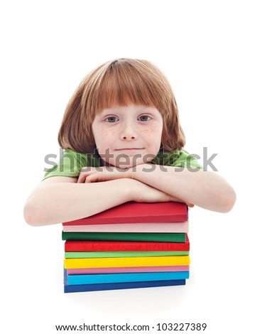 Little boy with freckles ready for school - leaning on book stack - stock photo