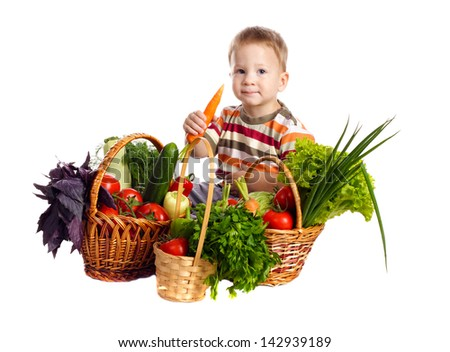 Little boy with fresh vegetables in baskets and carrot in hand, isolated on white - stock photo
