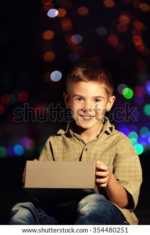Little boy with gift box on a blurred dark background - stock photo