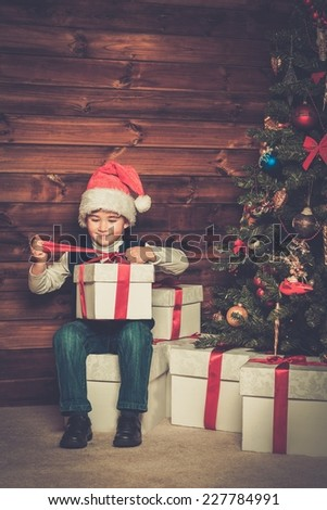 Little boy with gift box under christmas tree in wooden house interior  - stock photo