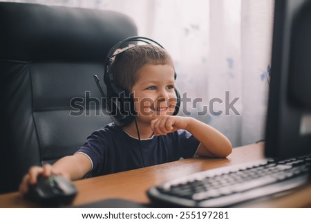 little boy with headset using computer, early education and learning