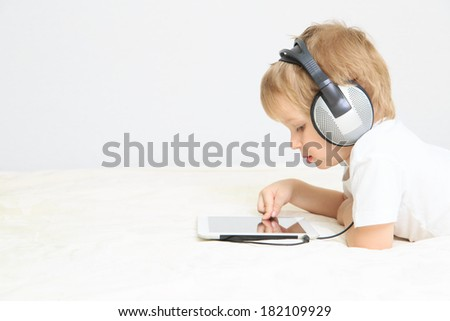 little boy with headset using touch pad, early education and learning - stock photo
