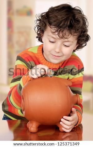 Little boy with his a big piggybank in house - stock photo