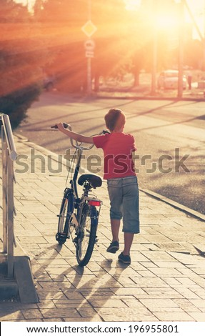 Little boy with his bike in a street backlit. Young boy riding bicycle on a summer day - stock photo