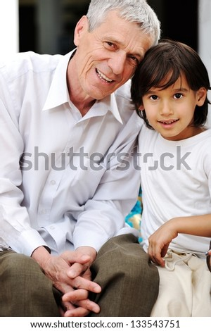 Little boy with his grandfather at home looking on the camera - stock photo