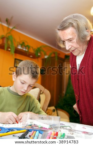 Little boy with his great grandmother are doing homework. Grandson and grandmother. Real situation. - stock photo