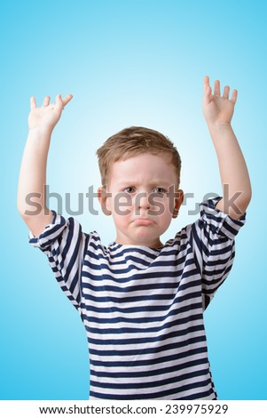 little boy with his hands raised offended on a blue background - stock photo