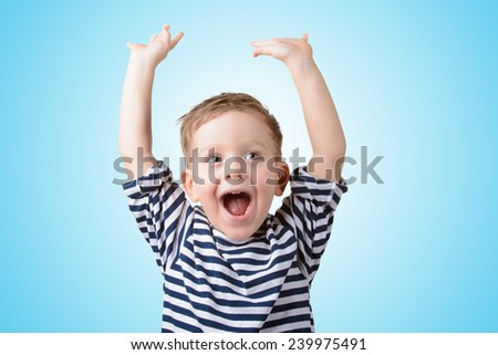 little boy with his hands up smiling on a blue background - stock photo