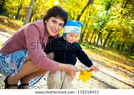 little boy with his mother walking in the autumn park - stock photo
