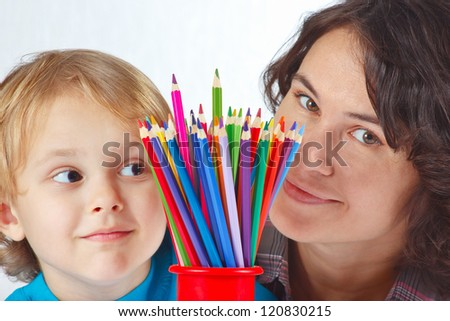 Little boy with his mother with color pencils on a white background - stock photo