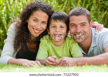 Little boy with his parents lying down in the garden