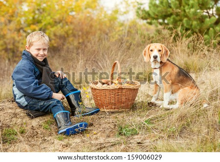 Little boy with his pet sit on clearing in the woods with basket full of mushrooms - stock photo
