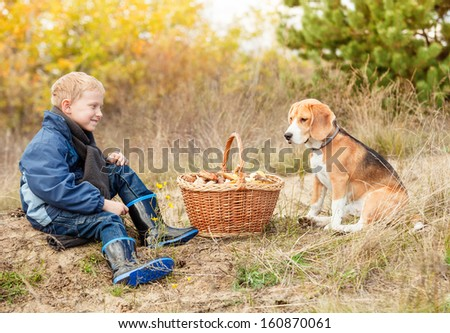 Little boy with his pet sit on forest glade with basket full of mushrooms - stock photo