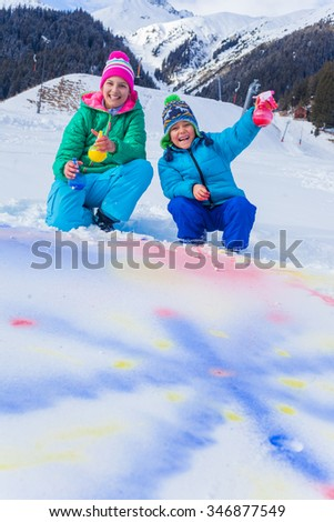 Little boy with his sister having fun in the snow - drawing on the snow - stock photo