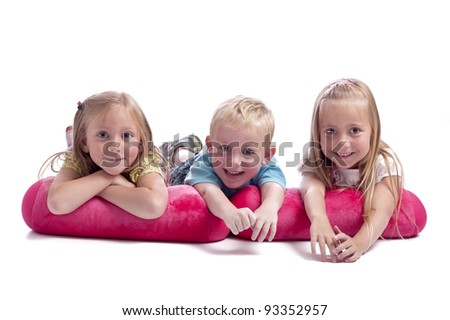 little boy with his 2 sisters. Lying on pink cushions. Isolated on white background - stock photo