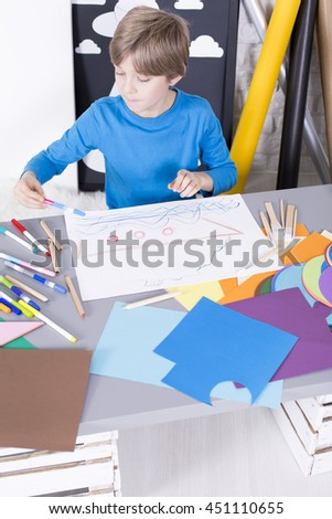 Little boy with imagination drawing a picture during art classes. On the desk colorful sheets of paper and pens