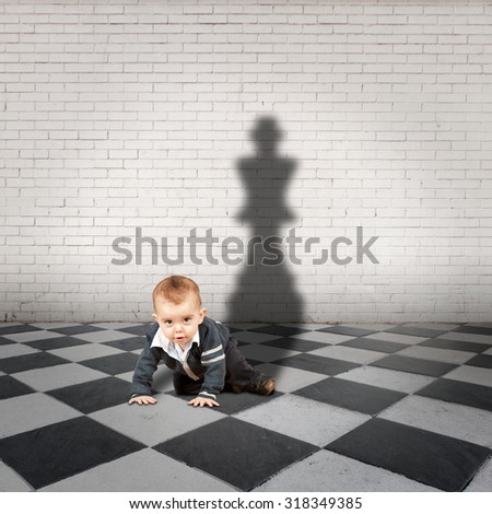 little boy with king shadow on a checkered floor - stock photo