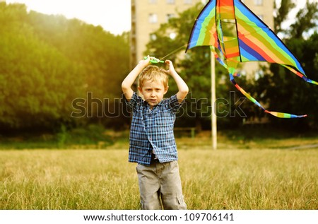 Little boy with kite flying over his head - stock photo