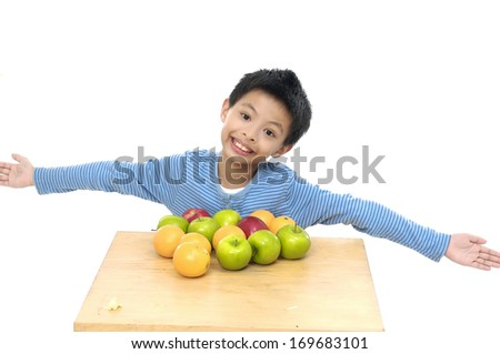 Little boy with many fruit at the Table - stock photo