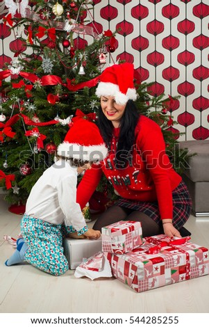 Little boy with mother opening Xmas gifts in front of Chritmas tree