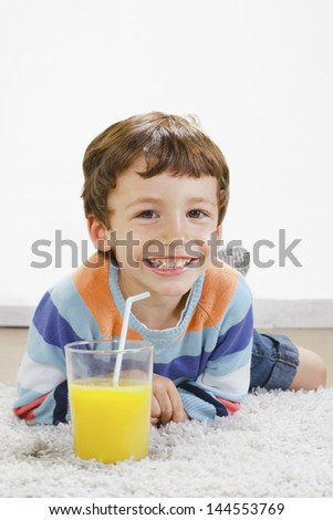 Little boy with orange juice stretching on carpet./ Child with breakfast in home. - stock photo