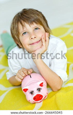 Little boy with piggy bank - stock photo