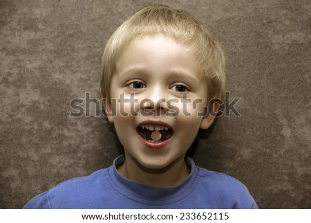 Little boy with pill in his mouth.