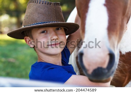 Little boy with pony closeup, outdoor portrait - stock photo