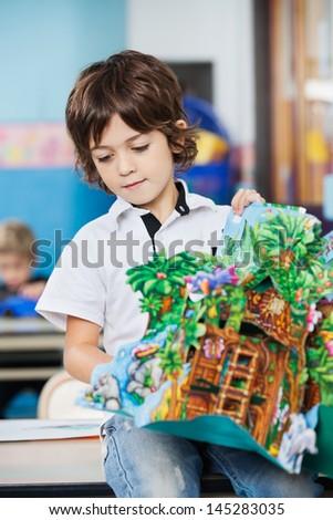 Little boy with popup book sitting on desk in kindergarten - stock photo