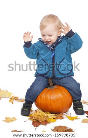 Little boy with pumpkin and autumn leaves