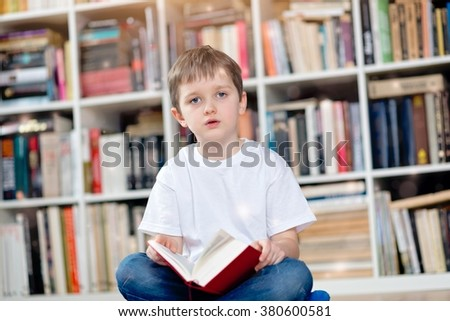 Little boy with red book in the library. Looking at camera. He sits cross-legged on the floor. Dressed in a white t shirt and blue jeans - stock photo