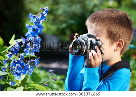 Little boy with retro camera shooting macro of blue flowers - stock photo