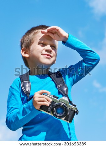 Little boy with retro SLR camera on blue sky looks into the distance