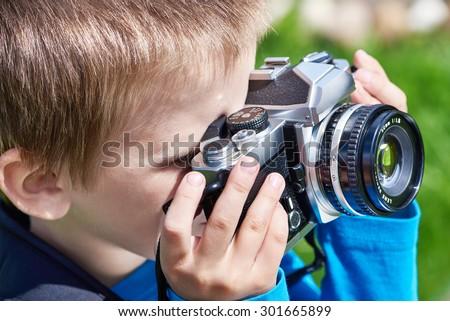 Little boy with retro SLR camera shooting - stock photo