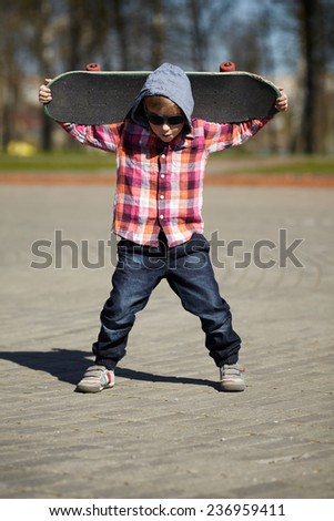 little boy with skateboard on the street - stock photo