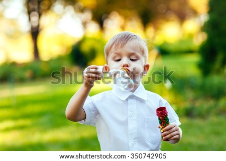 Little boy with soap bubbles in summer park. - stock photo