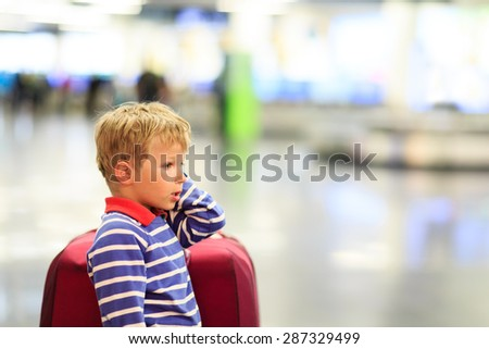 little boy with suitcase waiting in the airport, kids travel - stock photo
