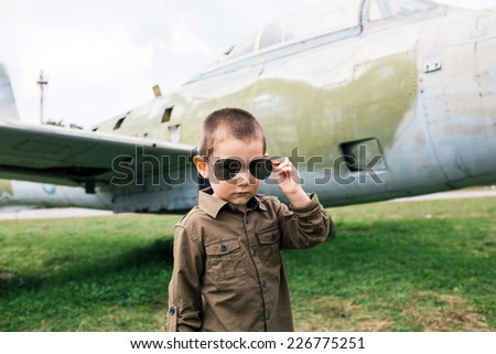 Little boy with sunglasses in front of airplane  - stock photo