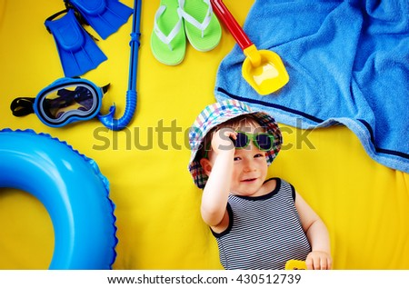 little boy with sunglasses in hat on yellow blanket