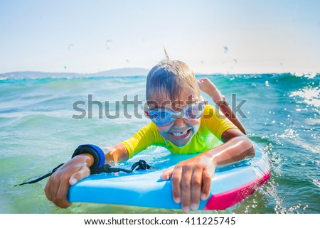 Little boy with surf board having fun in sea against sea - stock photo