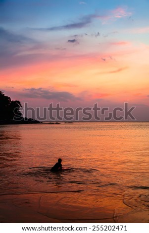 Little boy with surfboard at sunset on a beach - stock photo