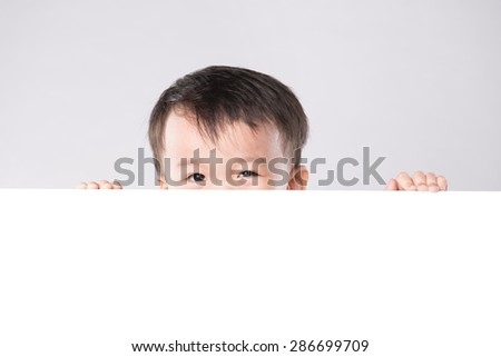 Little boy with surprise face behind the whiteboard - stock photo