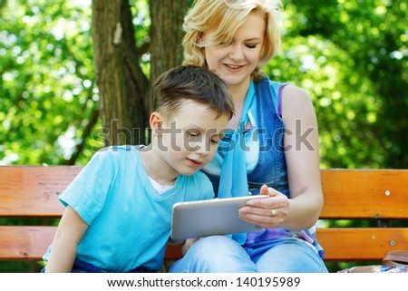 Little boy with tablet and mother, wireless technology, outdoor - stock photo