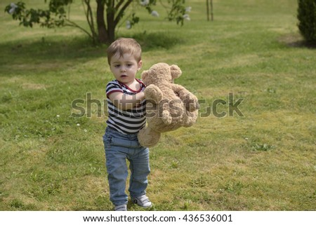 little boy with teddy bear outdoors